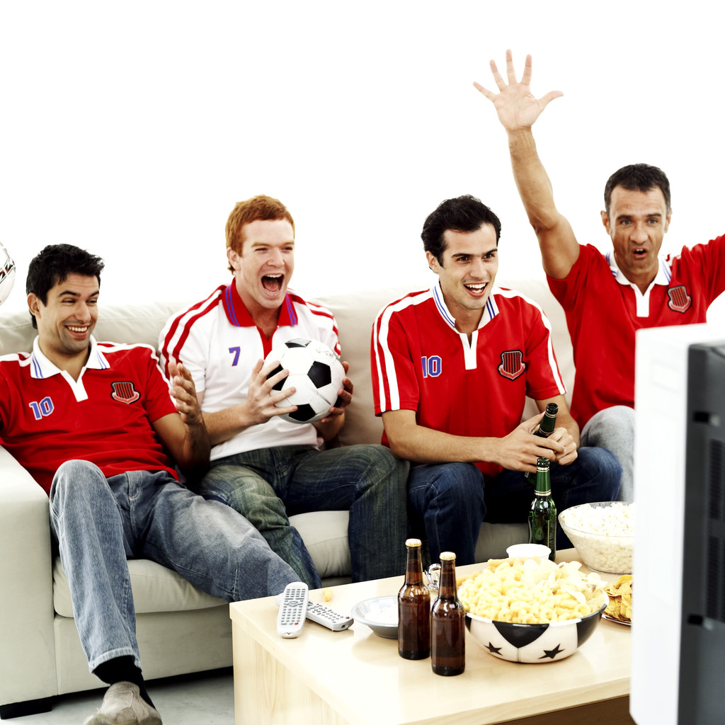 Group of Football Fans Sitting on a Couch and Watching the Game