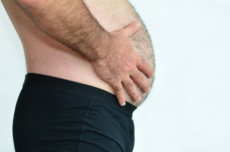 Man_holding_his_big_distended_bloated_belly